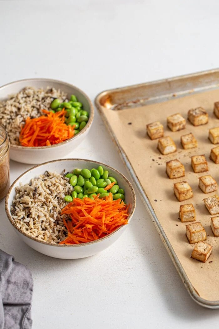 Bowl of rice, carrot and edamame sitting beside a baking tray of tofu.