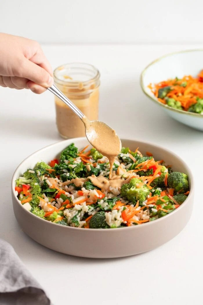 Hand adding a spoonful of peanut sauce to a kale salad.