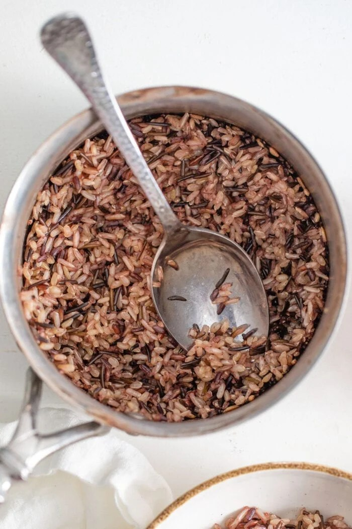Cooking wild rice in a pan.  The spoon rests in the pot.