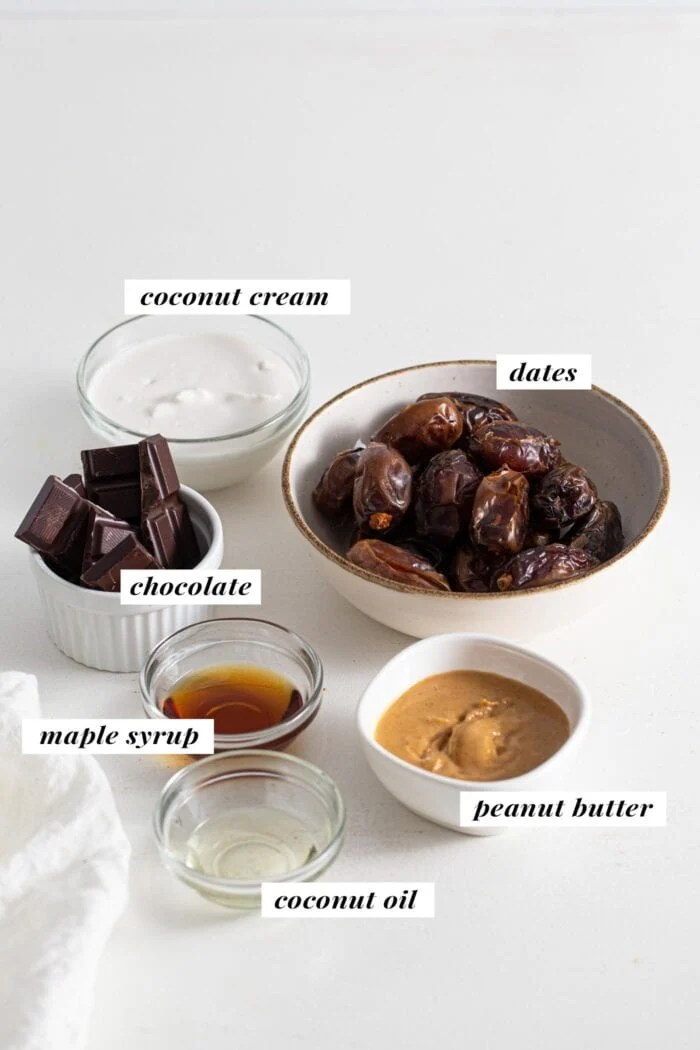 Dates, chocolate, peanut butter, coconut cream and maple syrup labelled in small glass dishes.