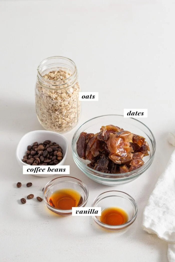 Oats, dates, coffee beans and vanilla in labelled containers.