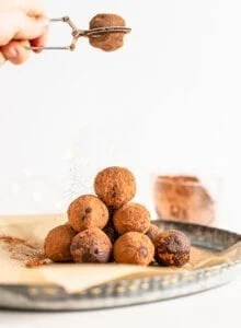 Stack of chocolate truffles on a plate being dusted with a sprinkling of cocoa powder.