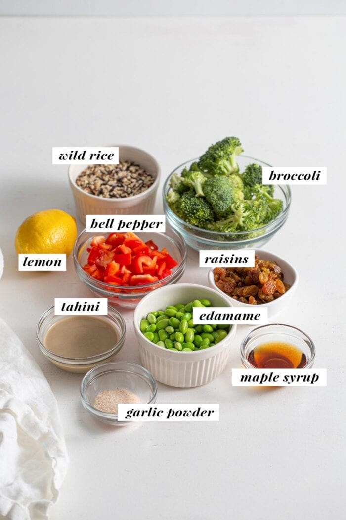 Rice, broccoli, lemon, tahini, edamame, maple syrup, raisins and chopped bell pepper in bowls. Labelled with text overlay.