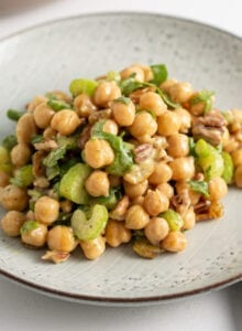 Curried chickpea salad with celery, walnuts and raisins on a plate.