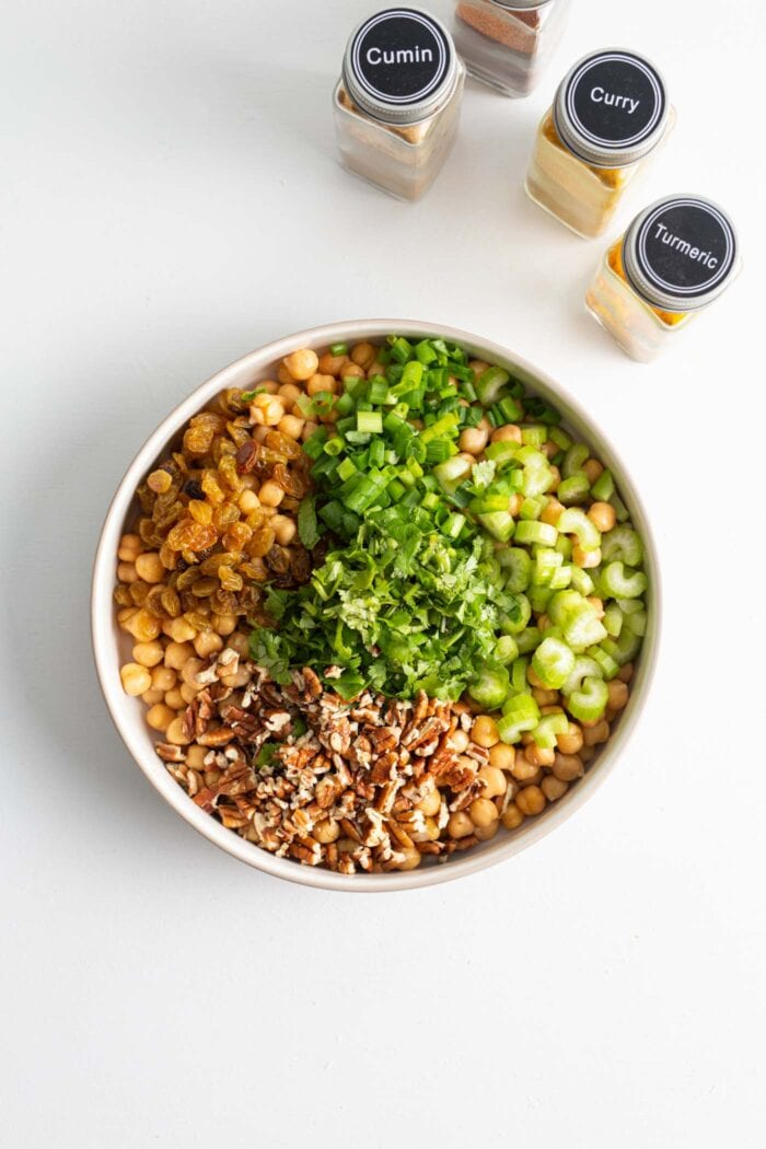 Walnuts, raisins, celery and green onion in a large salad bowl.