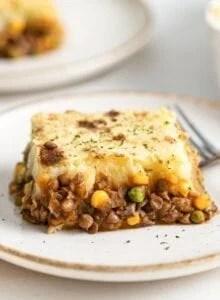 Slice of lentil shepherd's pie on a plate.