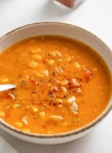 Close up of a sweet potato corn chowder in a bowl. Spoon rests in bowl.
