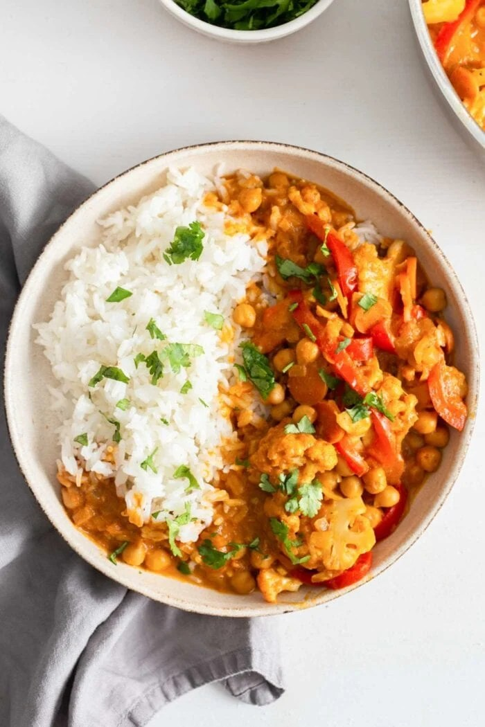 Bowl of white rice aside a cauliflower chickpea curry.