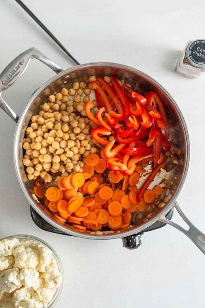 Chickpeas, chopped carrots and sliced bell peppers in a skillet cooking on a small stovetop.