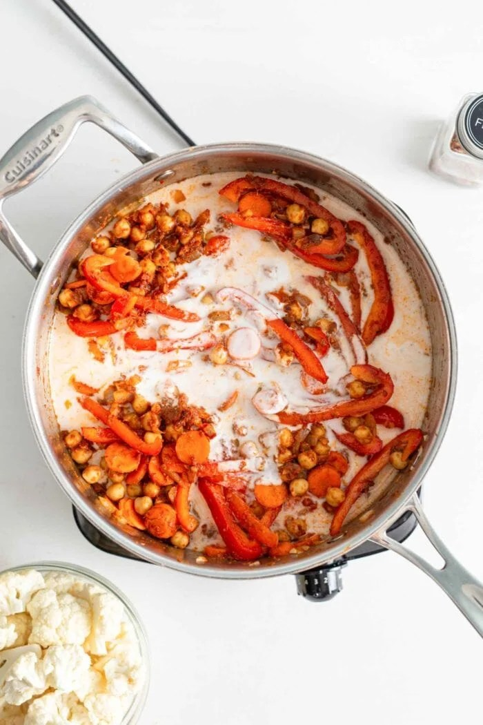 Chickpeas, bell peppers and carrots cooking in coconut milk in a skillet on a small cook top.