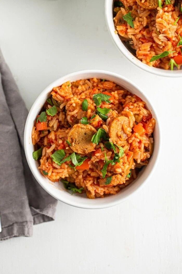 Overhead view of a bowl of jambalaya topped with a bit of fresh parsley.
