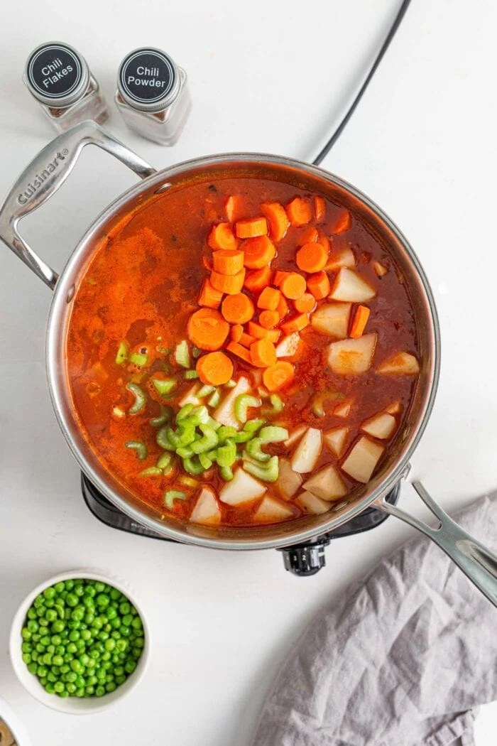 Tomato broth with chopped carrots, peas and potato cooking in a skillet.