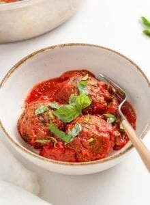 3 lentil meatballs with tomato sauce topped with fresh basil in a bowl.