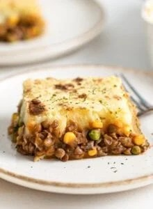 Large slice of lentil shepherd's pie on a plate.