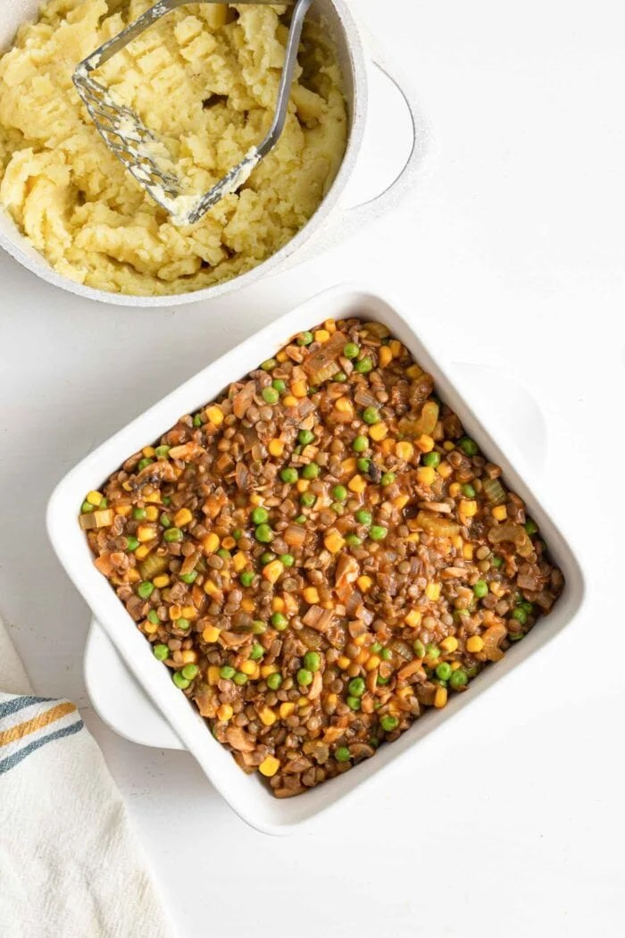Lentil shepherds pie filling in a baking dish before being topped with mashed potatoes.