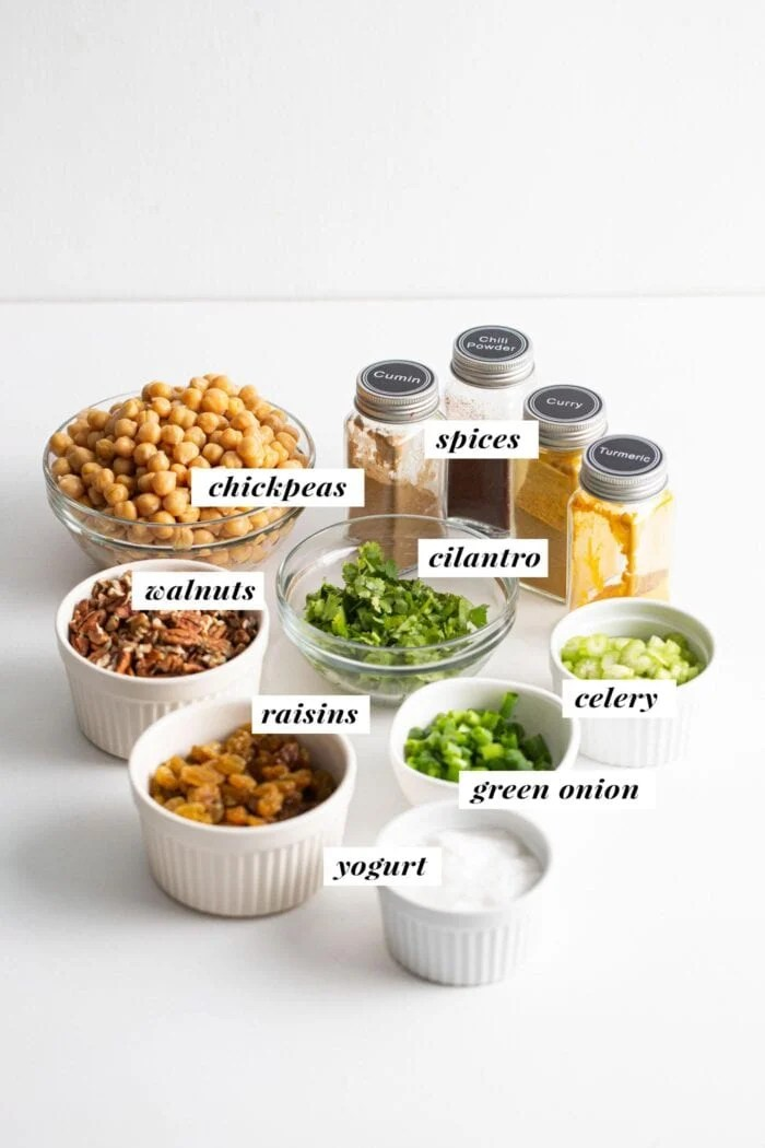 Visual of ingredients for making a curried chickpea salad recipe. Ingredients are labelled with text overlay.