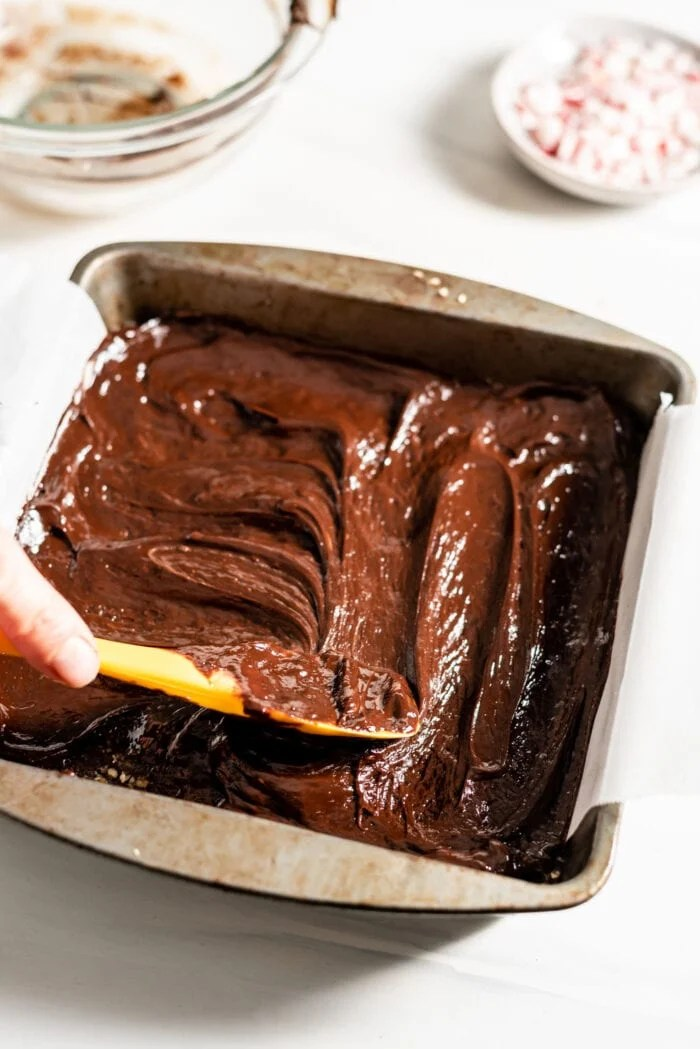 Hand using a spatula to spread melted chocolate in a baking pan.