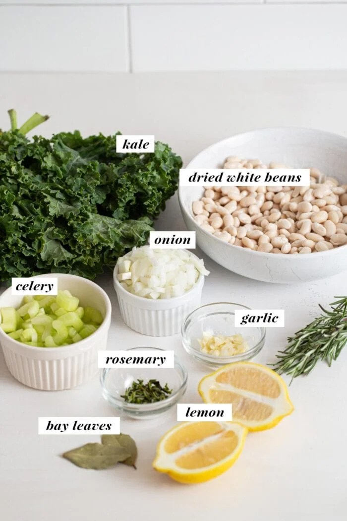 Visual of all ingredients needed for making a white bean and kale soup recipes. Ingredients are labelled with text overlay.