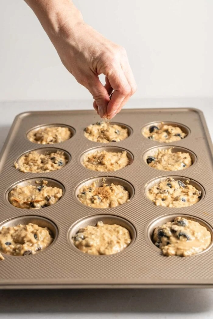 Sprinkling sugar on top of muffin batter in a muffin tin.