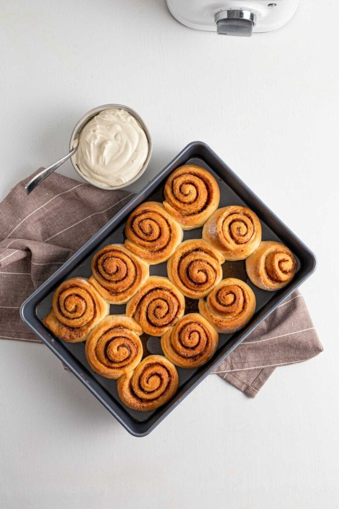 Overhead view of 12 baked cinnamon buns in a baking dish.