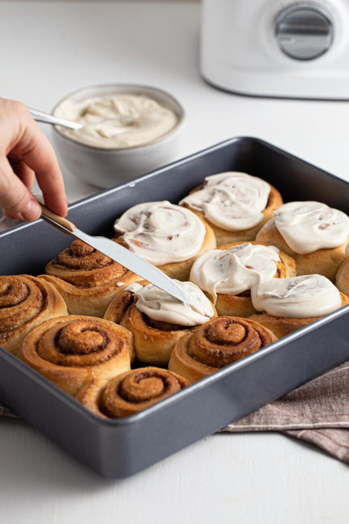 Hand holding a knife and frosting a baking dish of cinnamon rolls.