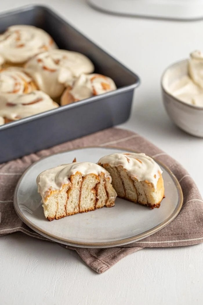 Sliced open cinnamon roll with frosting showing inside texture.