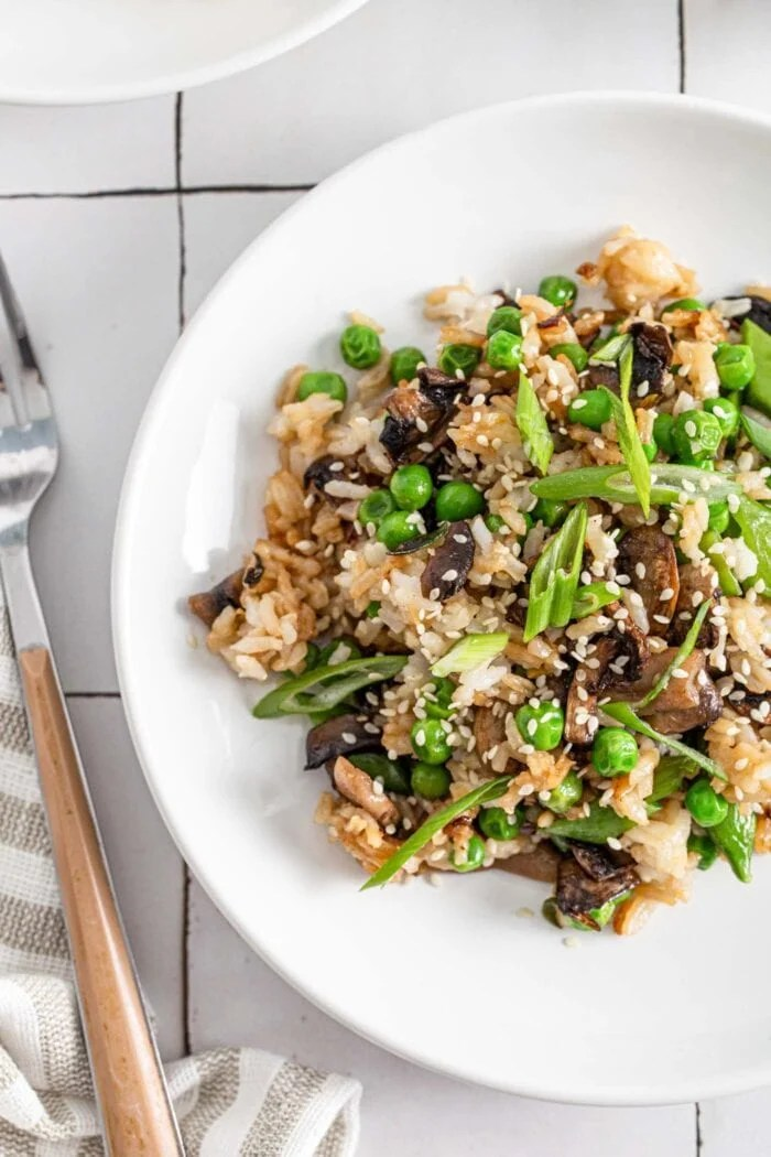 Overhead view of a plate of Chinese mushroom fried rice topped with sesame seeds and spring onions.