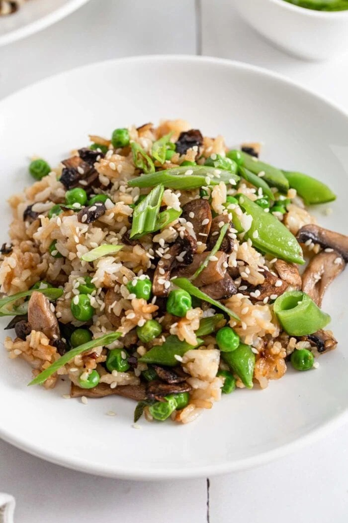 Plate of Chinese mushroom fried rice topped with sesame seeds and spring onions.