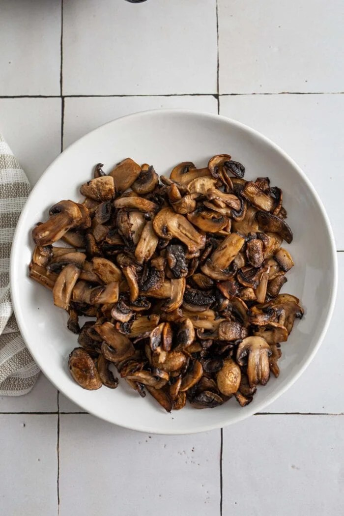 Cooked browned mushrooms on a plate.