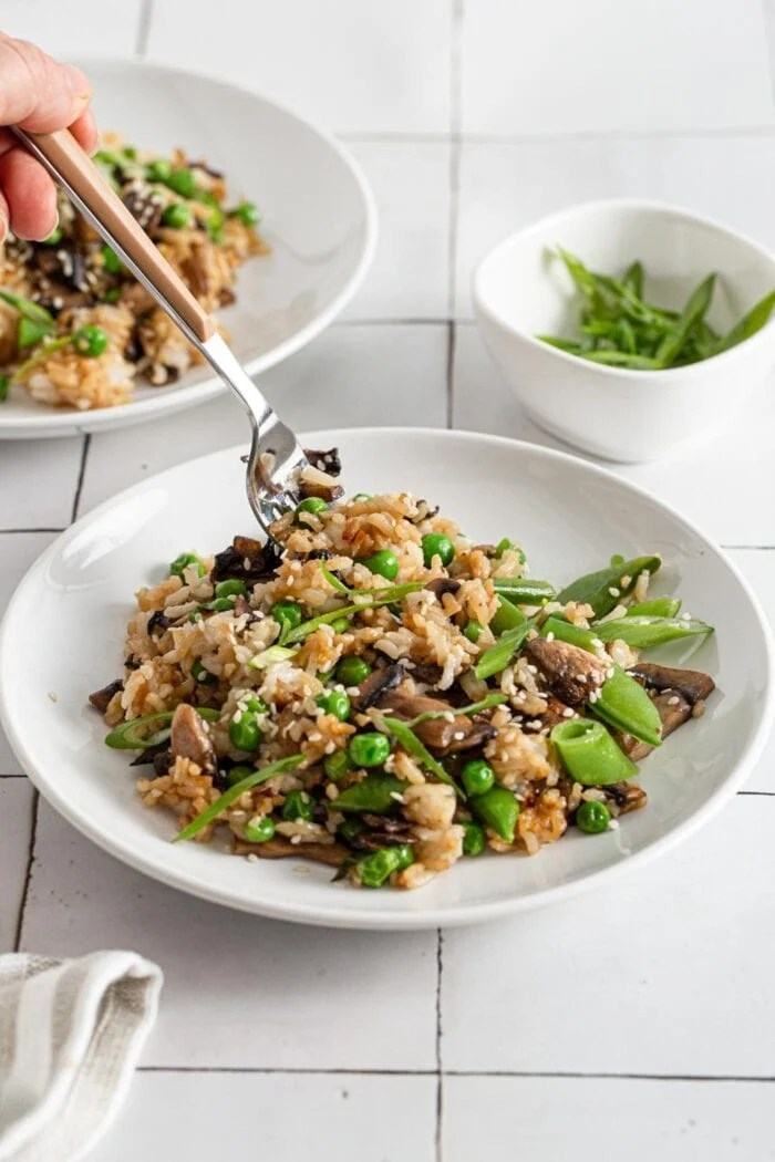 Hand with a fork taking a forkful of vegan mushroom fried rice.