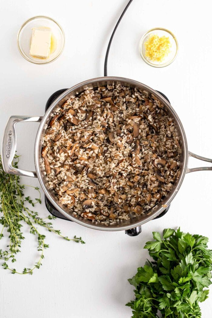 Rice and mushrooms cooking in a small skillet on a cooktop.