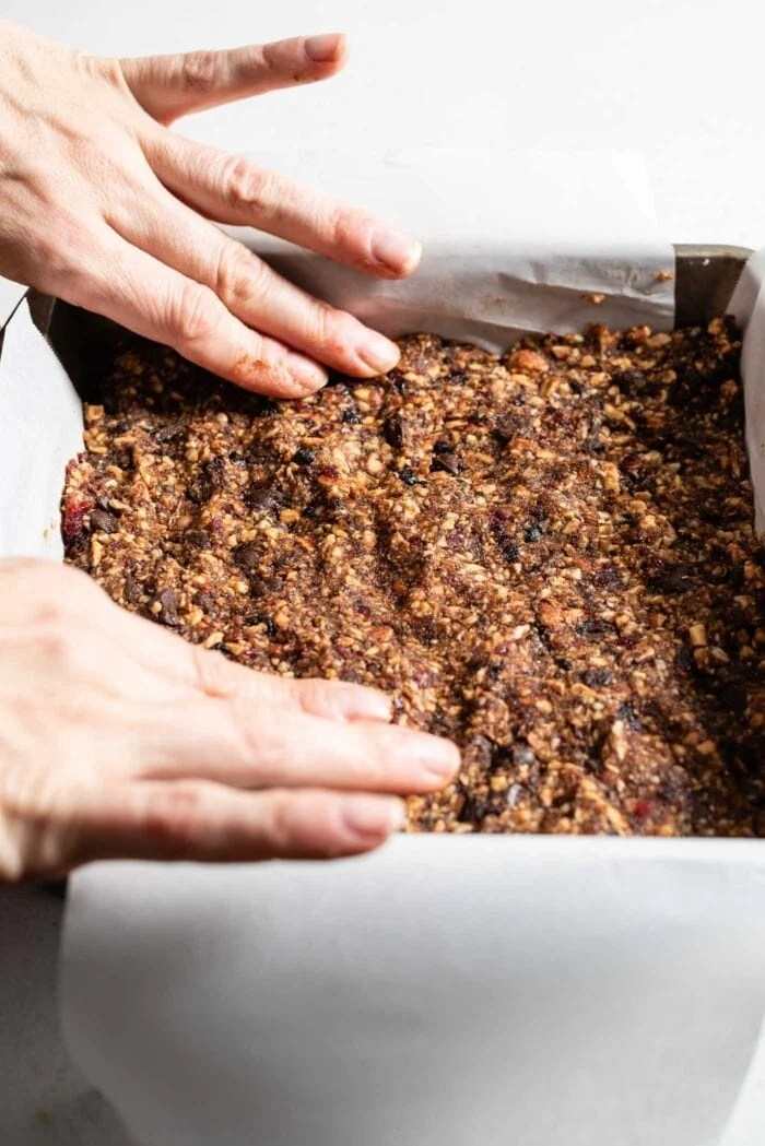 Two hands pressing raw energy bar dough into a baking pan.