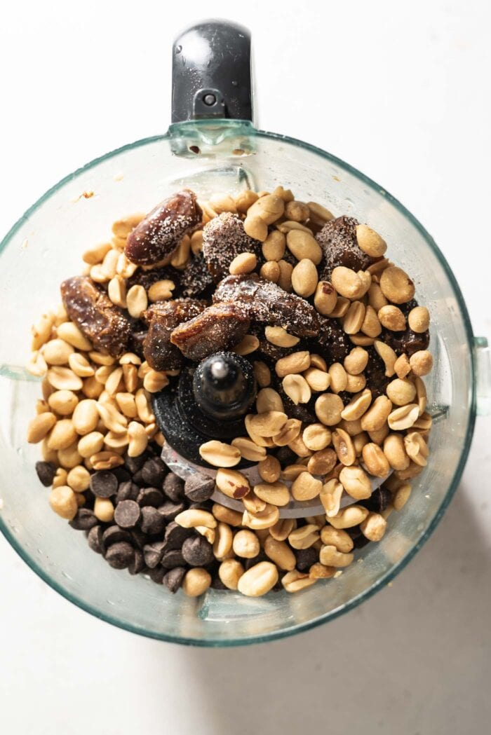 Peanuts, chocolate chips and dates in a food processor.