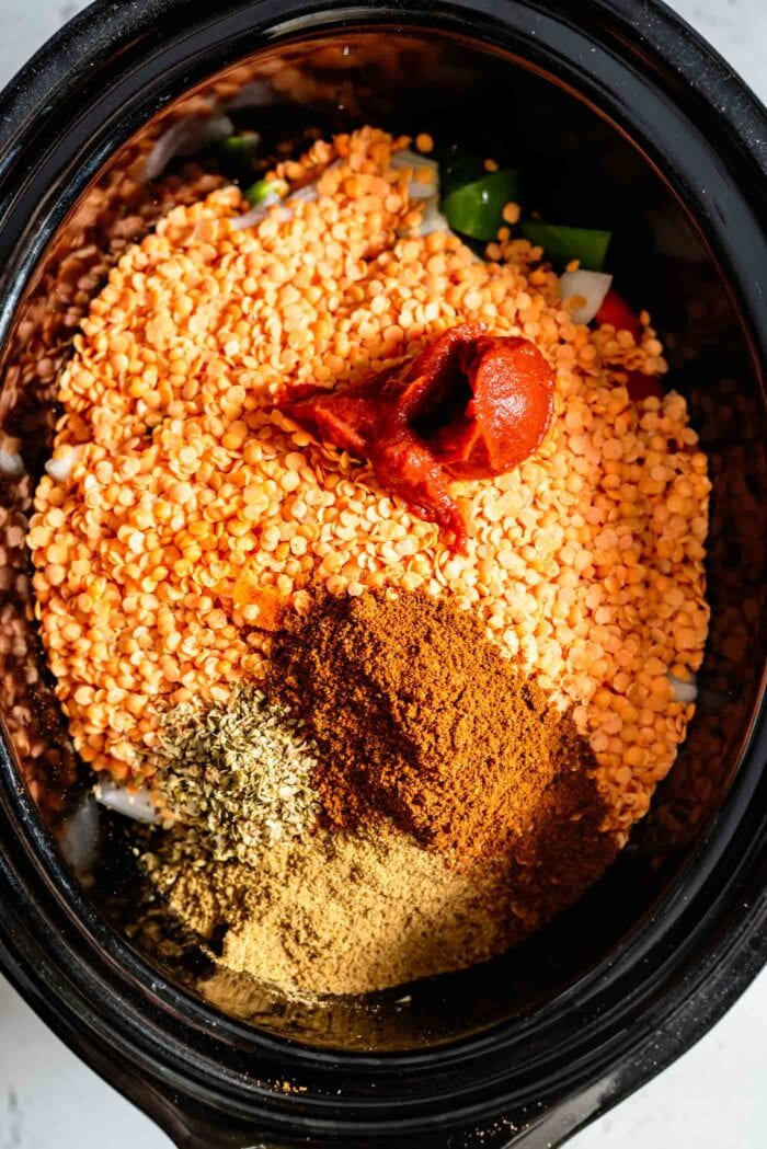 Red lentils, spices and tomato paste in a crockpot.