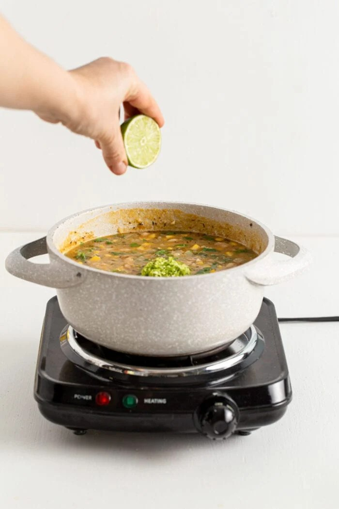 Squeezing lime into a pot of white bean chili.