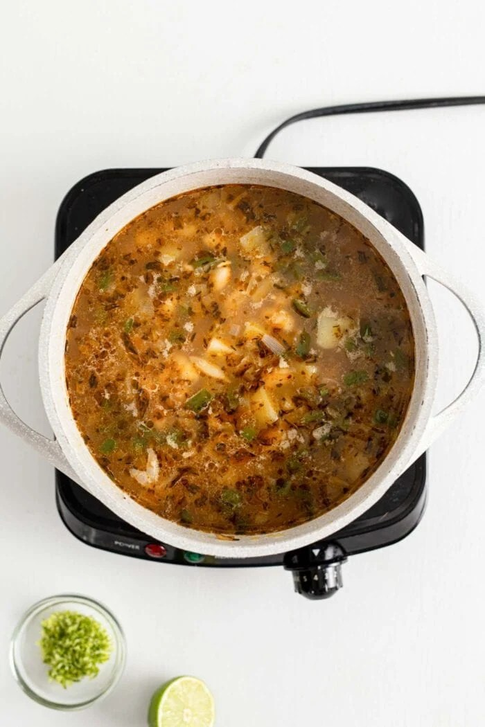 Soup with beans and potato cooking in a large pot on a small induction cook top.
