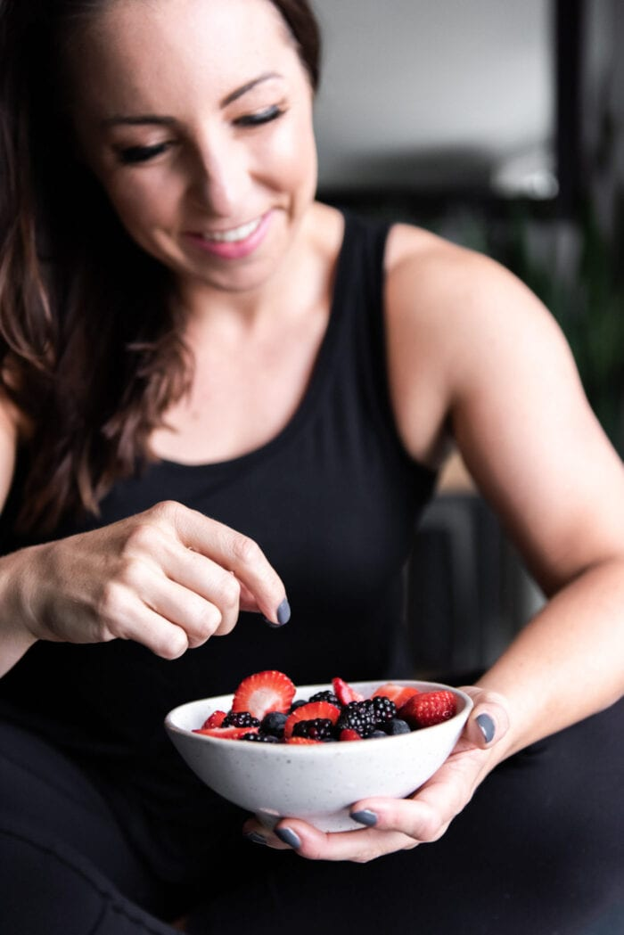 Woman holding a bowl of berries.