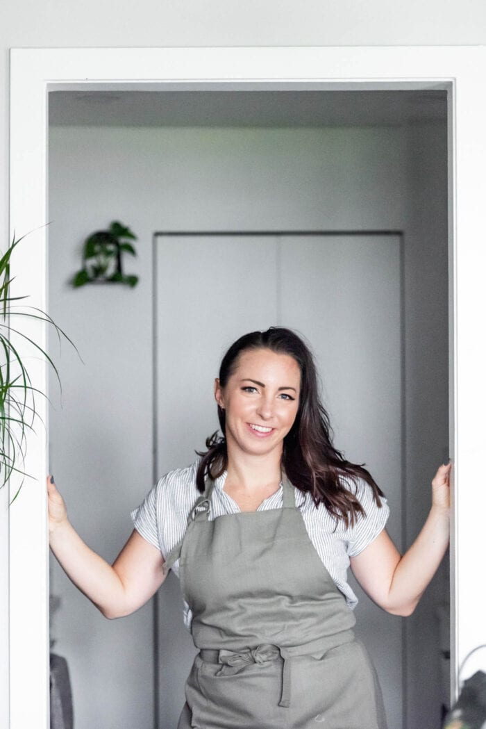 Woman wearing an apron standing in a door frame in front of a kitchen.