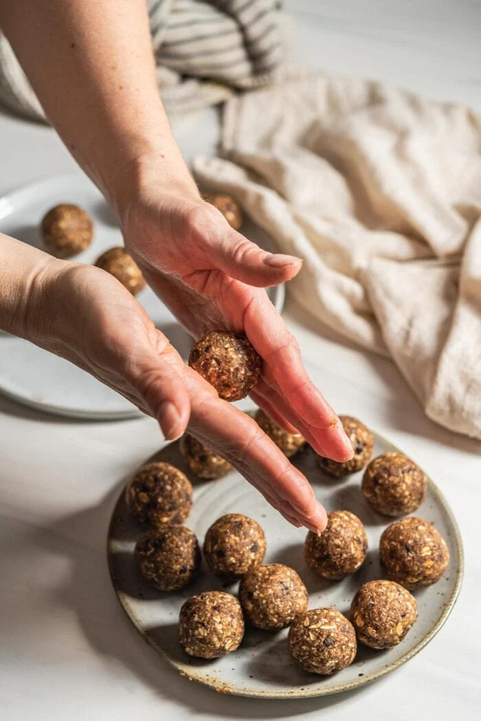 Two hands rolling energy ball dough into balls.