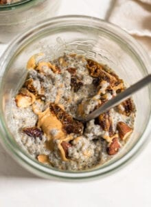 Overhead view of a jar of chia seed pudding with almonds, dates and peanut butter.