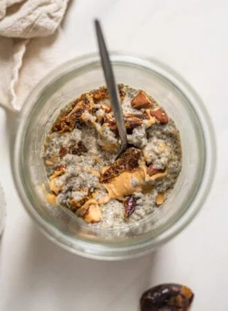 Overhead view into a jar of chia seed pudding with peanut butter, dates and almonds.