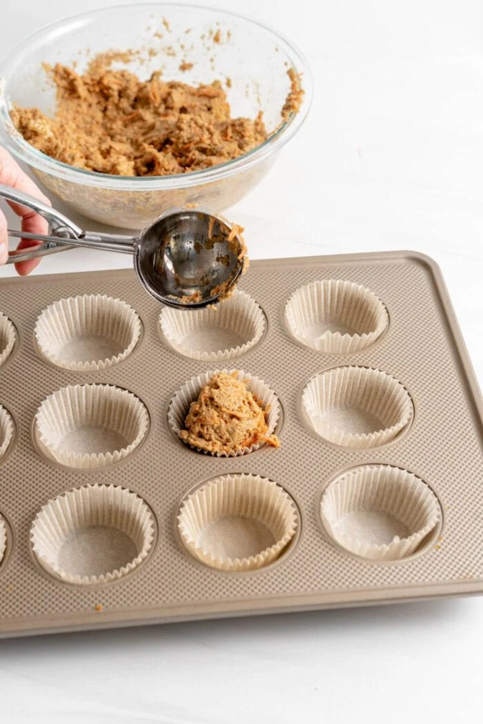 Scooping raw muffin batter into muffin liners in a muffin pan.