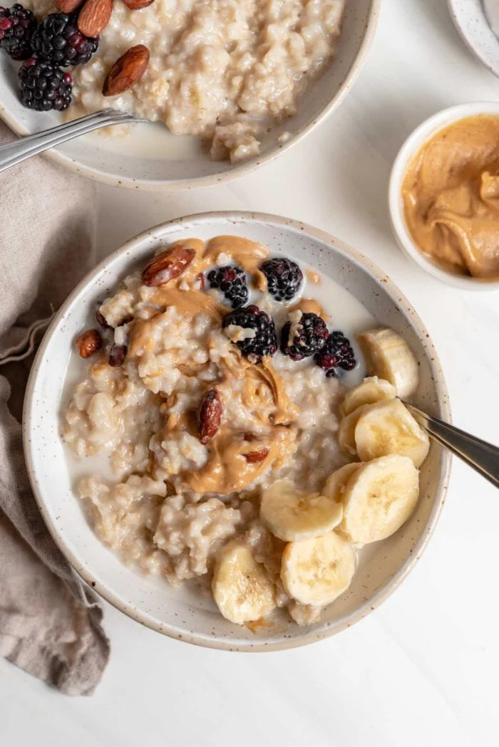 Bowl of oatmeal topped with peanut butter, banana and berries.