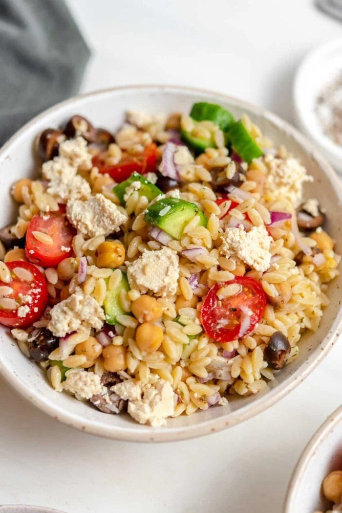 Close up of a bowl of Mediterranean orzo salad with tomato, cucumber and olives.