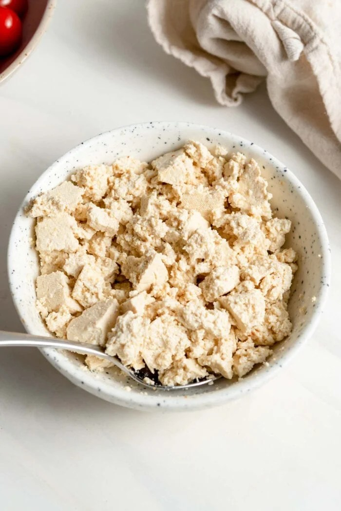 Crumbled tofu in a small bowl with a spoon.