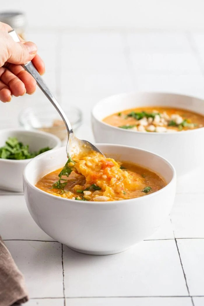 Hand using a spoon to take a spoonful of mulligatawny from a bowl.