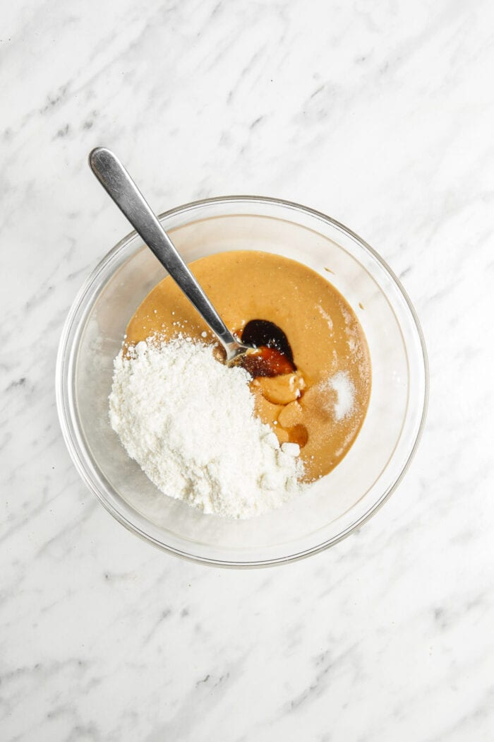 Coconut flour, maple syrup and peanut butter in a mixing bowl with a spoon.