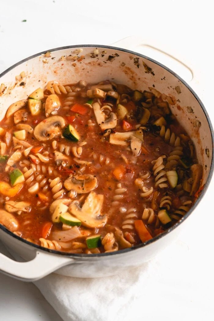 Rotini and vegetables cooking in tomato sauce in a pot.