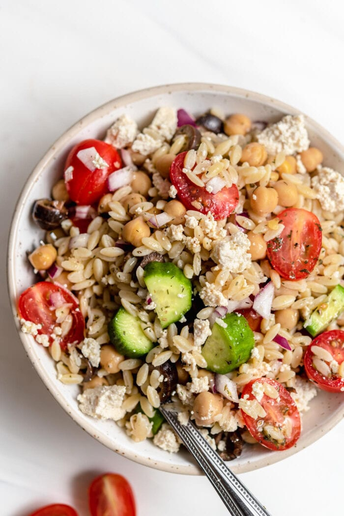 Overhead view of bowl of Mediterranean orzo salad with tomato, cucumber and olives.
