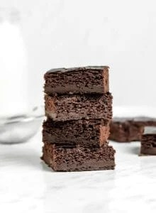 Front view of a stack of 4 sweet potato brownies sitting on a marble surface.